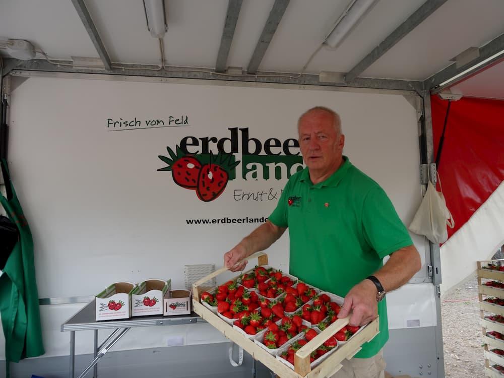 Verkäufer baut Erdbeerverkaufsstand auf